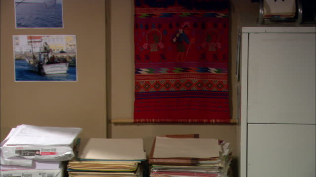 CLOSE ANGLE OF OFFICE. PILES OF PRINTER PAPER, FOLDERS, AND FILES LAY ON TABLE AGAINST WALL. FILE CABINET VISIBLE TO RIGHT. BOAT PICTURES AND CLOTH ART HANG ON WALL.