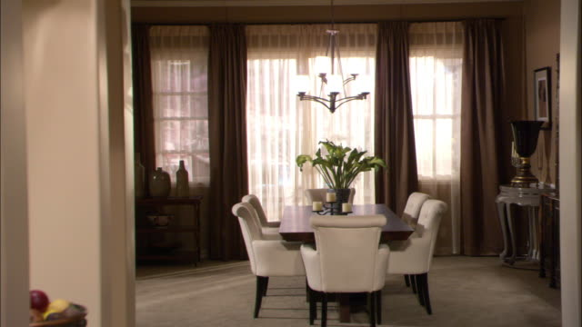 WIDE ANGLE OF DINING ROOM. DINING ROOM TABLE WITH SIX LEATHER CHAIRS VISIBLE IN CENTER OF ROOM. DECORATIVE LIGHT FIXTURE HANGS ABOVE TABLE. VASE WITH FLOWERS AND CANDLES ARE ON TABLE. UPPER CLASS.