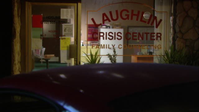 MEDIUM ANGLE OF 'LAUGHLIN CRISIS CENTER FAMILY COUNSELING' BUILDING. LIGHTS ARE TURNED ON IN OFFICE. FILE CABINET AND DESK VISIBLE THROUGH WINDOW. CAR ROOF VISIBLE IN FG.