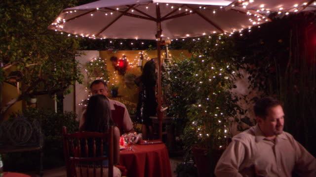 vídeos de stock e filmes b-roll de medium angle of outdoor restaurant area. pov pans right to left over men and women sitting at tables in restaurant patio. - empregado de mesa