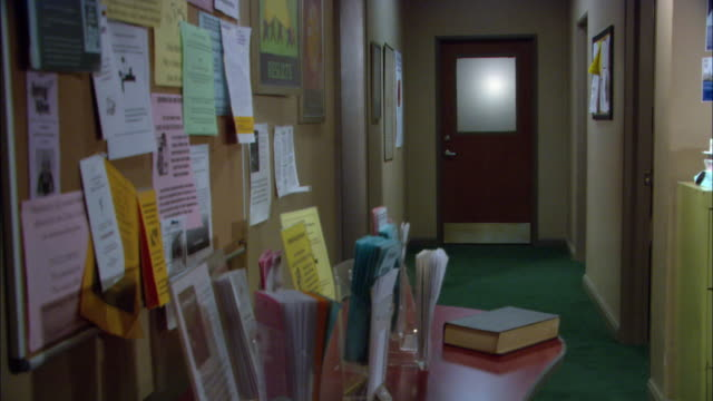 MEDIUM ANGLE OF DARK HALLWAY OR CORRIDOR IN OFFICE. TABLE COVERED WITH PAMPHLETS VISIBLE IN FG. BULLETIN BOARD ON WALL TO LEFT. COULD BE USED AS A SCHOOL OR COUNSELING BUILDING.