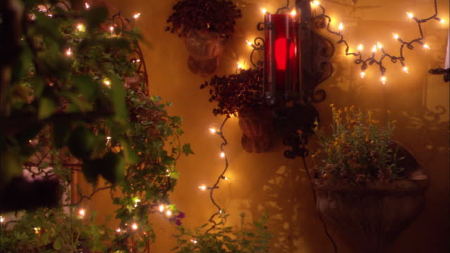 medium angle of lights and plants decorating yellow wall. could be used for a home gazebo pool area or festive restaurant. - gazebo stock videos & royalty-free footage