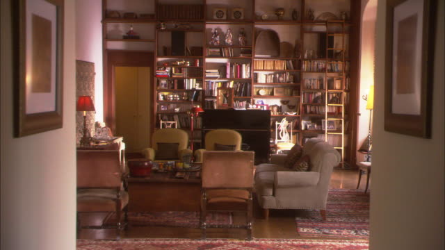 vídeos de stock, filmes e b-roll de wide angle zoom in of living room or den. shelves filled with books and figurines cover far wall. upright piano couches and coffee table visible inside room. could be used as a personal library. - ornamento