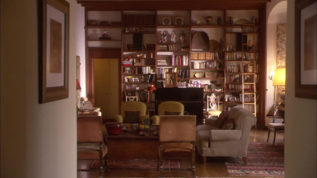vídeos de stock, filmes e b-roll de wide angle of living room or den. shelves filled with books and figurines cover far wall. upright piano couches and coffee table visible inside room. could be used as a personal library. - esetante de livro