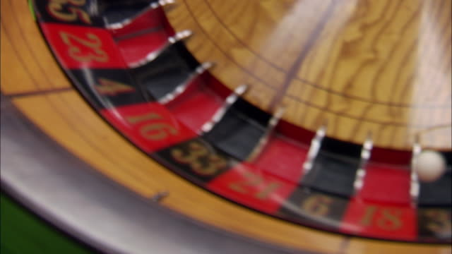 close angle of spinning roulette wheel. follow ball as it rolls round and round and stops in red space. man's hand picks up ball and throws it again. gambling. green screen visible in background. - roulette wheel stock videos and b-roll footage