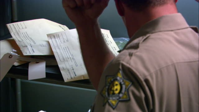 MEDIUM ANGLE OF POLICE OFFICER STANDING NEXT TO SHELVES FILLED WITH ENVELOPS. OFFICER TAKES ONE ENVELOPES AND PLACES IT ON NEARBY DESK WITH PHONE. ENVELOPES COULD CONTAIN EVIDENCE OR PERSONAL PROPERTY FOR PEOPLE IN JAIL. MEN.