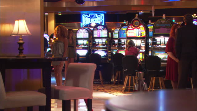 wide angle of people playing slot machines in a casino. lamp sits on a table in foreground. a waitress in short gray dress starts to walk through frame. gambling. - casino interior stock videos & royalty-free footage