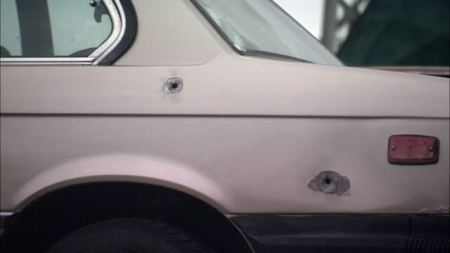 MEDIUM ANGLE OF BULLETS BEING FIRED INTO REAR SIDE OF COMPACT CAR. TWO BULLET HOLES ALREADY VISIBLE. TWO MORE SHOTS HIT REAR WINDOW AND REAR SIDE PANEL. OVERCAST IN BG. GUNFIRE, GUNSHOTS.