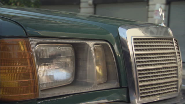 close angle of front right headlight and radiator grille of mercedes-benz  as it drives down downtown urban street, possibly los angeles. tall buildings in bg. headlight is off. - mercedes benz stock videos & royalty-free footage