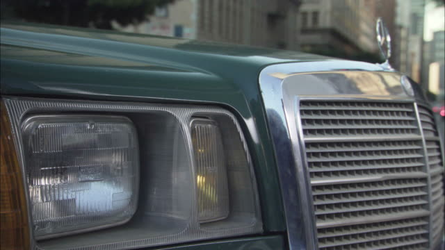 close angle of front right headlight, grill, and hood of mercedes as it drives down downtown urban street, possibly los angeles. - mercedes benz stock videos and b-roll footage