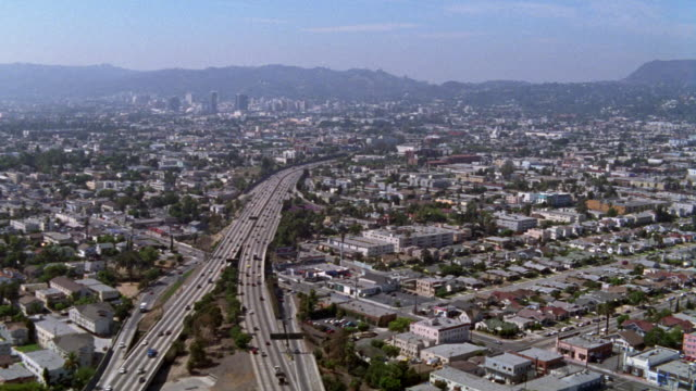vídeos de stock, filmes e b-roll de aerial of city of los angeles city. various office buildings, multi-story buildings and high rise buildings. 110 freeway into downtown visible. house and apartment buildings. urban area. mountains in bg. blue skies. - 1990 1999