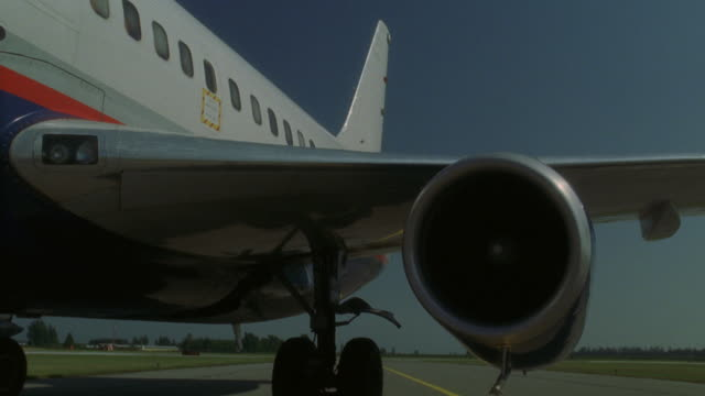 stockvideo's en b-roll-footage met steadicam shot of parked airplane engine and wing of the aircraft. jet is commercial (r156-2 through r158-10 match) - opeenvolgende serie