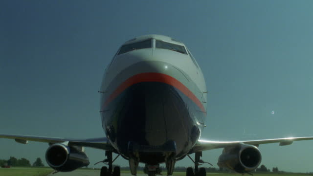 stockvideo's en b-roll-footage met close angle of the nose of commercial jet or airplane as it sits on the ground. pan to underneath the plane to fake or simulate the plane lifting off taking off. (r156-2 through r158-10 match) - opeenvolgende serie