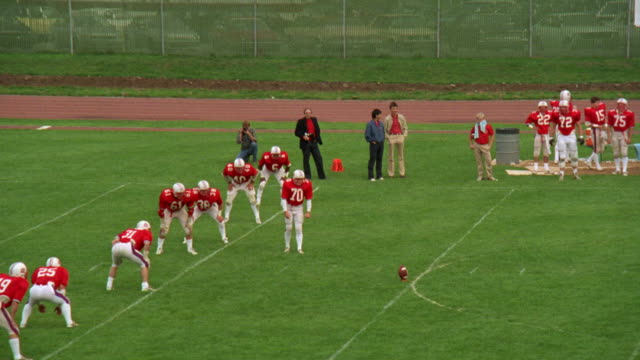 medium angle of opening kick-off play during high school football game. see team kicking in red and white uniforms. see receiving team in yellow and blue prepare to catch and run ball. - anno 1985 video stock e b–roll