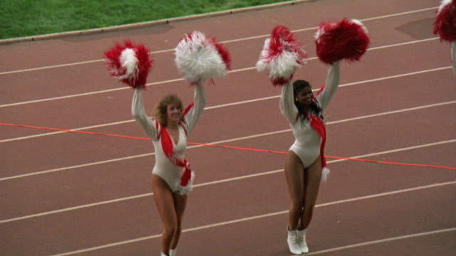 MEDIUM ANGLE OF CHEERLEADERS IN RED AND WHITE UNIFORMS CHEERING AT HIGH SCHOOL FOOTBALL GAME. SEE CHEERLEADERS WITH POM POMS STAND ON TRACK AND APPEAR TO HAVE 80'S STYLE HAIRCUTS AND UNIFORMS.