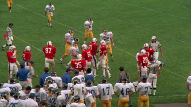 MEDIUM ANGLE OF RUNNING PLAY AT HIGH SCHOOL FOOTBALL GAME.  SEE DEFENSIVE  TEAM  DRESSED IN RED AND WHITE UNIFORMS. SEE OFFENSIVE TEAM DRESSED IN YELLOW AND BLUE UNIFORMS.