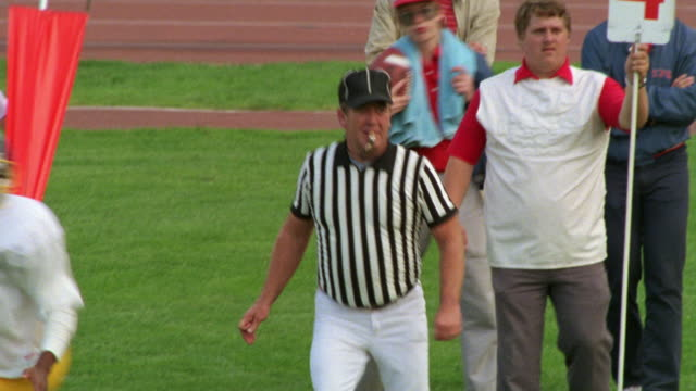MEDIUM ANGLE OF REF OR REFEREE DRESSED IN BLACK AND WHITE AT HIGH SCHOOL FOOTBALL GAME. SEE DEFENSIVE  TEAM  DRESSED IN RED AND WHITE UNIFORMS.