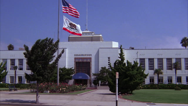 wide angle of santa monica city hall. could be courthouse, city hall, town hall, municipal building, or government building. american and california flags waving on flag poles in front of building. - 法廷点の映像素材/bロール