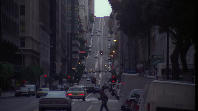 vídeos y material grabado en eventos de stock de wide angle downtown business street in san francisco. commercial area.  hill in bg. cars drive on street. cars parked on curb. pedestrians. office buildings and apartment buildings line street. - 1985