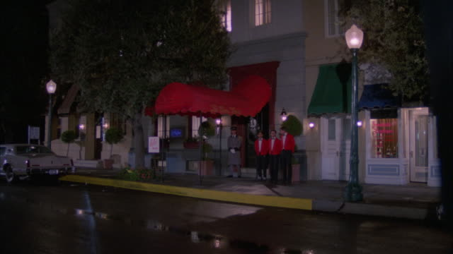 "wide angle of upper  class french restaurant. red awning over entrance. sign on awning reads ""le bon gout."" could be cocktail lounge. valets and doorman wait at entrance. - awning stock videos and b-roll footage"