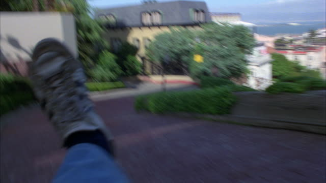 medium angle moving pov of lombard street in san francisco. could be in car or on bike. sharp turns. brick or cobblestone street. steep hill. bay and city in bg. residential area. apartment buildings. - lombard street san francisco stock videos & royalty-free footage