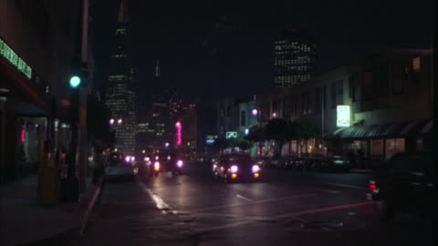 pan right to left of san francisco business street as vintage mercedes limousine drives by. bars and clubs line road. neon lights. pedestrians on sidewalk. transamerica building in bg. - mercedes benz markenname stock-videos und b-roll-filmmaterial