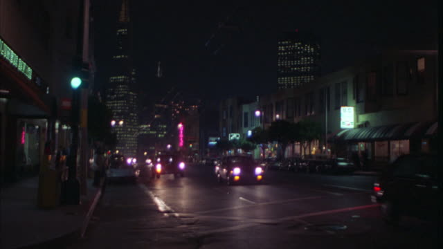 pan right to left of san francisco business street as vintage mercedes limousine drives by. bars and clubs line road. neon lights. pedestrians on sidewalk. transamerica building in bg. - limousine stock videos & royalty-free footage