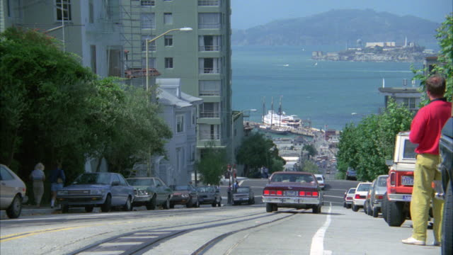 PAN RIGHT TO LEFT AS BROWN CADILLAC DRIVES UP STEEP STREET OR HILL IN SAN FRANCISCO. ALCATRAZ VISIBLE IN BG. BAY AND HARBOR IN BG. FERRY. TOWNHOUSES AND APARTMENTS LINE STREET.