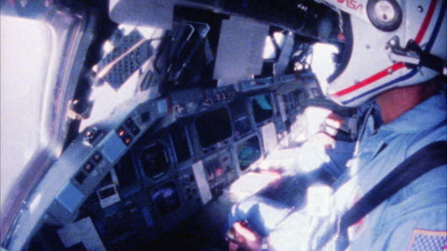 CLOSE ANGLE OF INTERIOR OF ROCKET. ASTRONAUT OR PILOT WITH AMERICAN FLAG PATCH ON SHOULDER SITS IN COCKPIT OF SPACESHIP OR SPACE SHUTTLE. NASA.