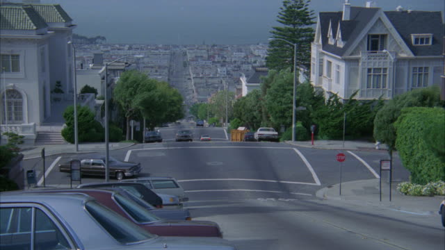 PAN LEFT TO RIGHT AS BROWN CADILLAC DRIVES UP STEEP STREET OR HILL IN SAN FRANCISCO.  TOWNHOUSES AND APARTMENTS LINE STREET. BAY VISIBLE IN BG.