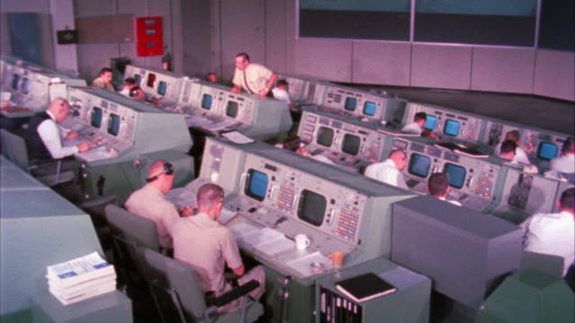 MEDIUM ANGLE OF CONTROL CENTER OR MISSION CONTROL AT NASA. MEN SITTING AT CONTROL PANELS WATCHING MONITORS.