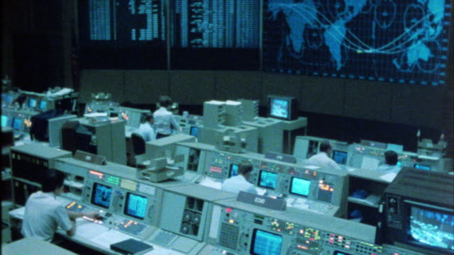 pan right to left of interior  of nasa space control center. men sit at control panels. map of earth on monitor. could be mission control. - nasa video stock e b–roll