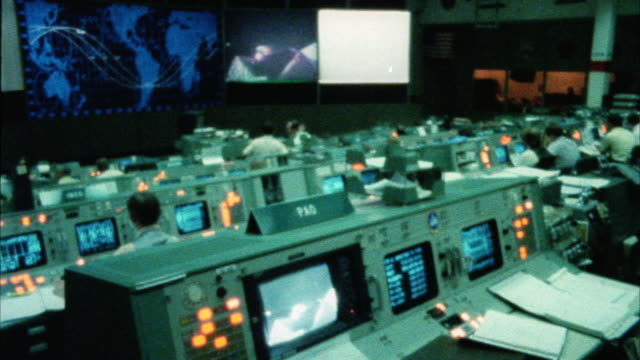 stockvideo's en b-roll-footage met wide angle of interior  of nasa space control center. men sit at control panels. map of earth on monitor. could be mission control. - regelkamer