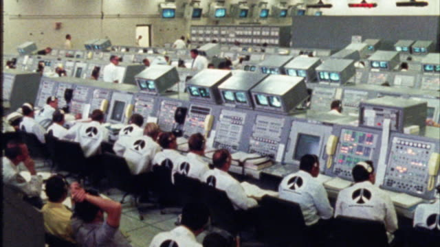 wide angle of interior  of nasa space control center. men sit at control panels. could be mission control. insignias on coats. - sala di controllo video stock e b–roll