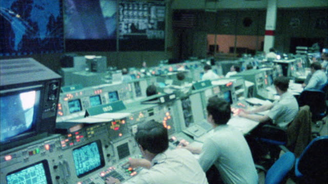 medium angle space control center or mission control room.  men working at control panels. maps on monitors. could be nasa. - razzo spaziale video stock e b–roll