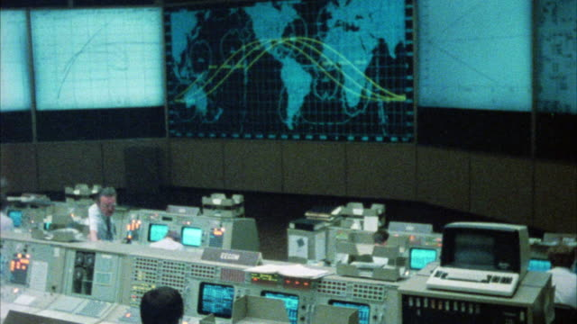 PAN RIGHT TO LEFT SPACE CONTROL CENTER OR MISSION CONTROL ROOM.  MEN WORKING AT CONTROL PANELS. MAPS ON MONITORS. COULD BE NASA.