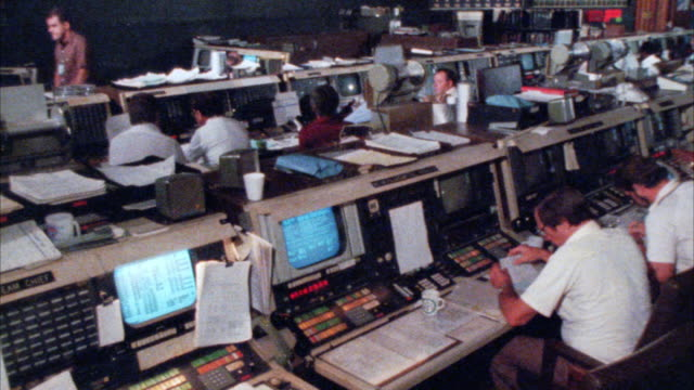 medium angle of space control center or mission control room.  men working at control panels. - nasa video stock e b–roll