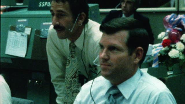 close angle of control center or mission control at nasa. men sitting at control panels watching monitors. - nasa stock videos & royalty-free footage