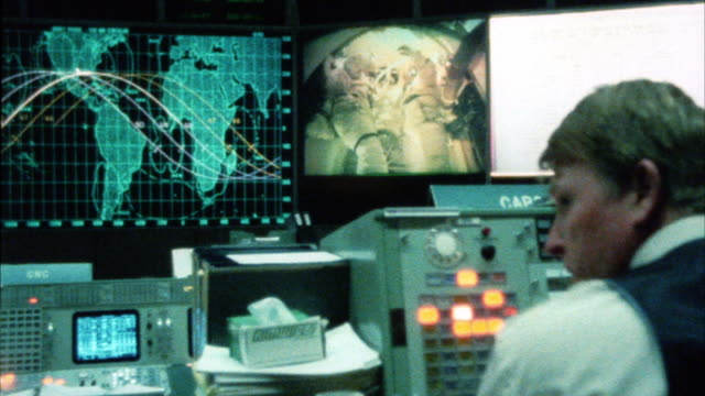 close angle of control center or mission control at nasa. men sitting at control panels watching monitors. maps on monitor. video from interior of space shuttle. astronauts. cut back to control room. - sala di controllo video stock e b–roll