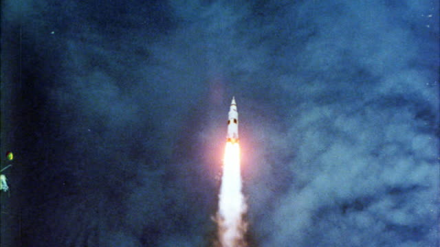 up angle as rocket or space shuttle travels towards space. blue sky and clouds. flames and smoke left as exhaust. saturn v rocket. spaceships. nasa. fire or flames trail behind. - spazio cosmico video stock e b–roll