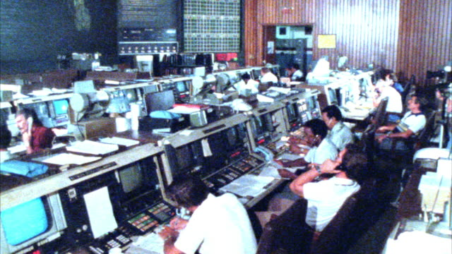 "medium angle of space control center or mission control room.  men working at control panels. camera pans up to map of earth on monitor. sign above map reads ""goddard network."" - sala di controllo video stock e b–roll"