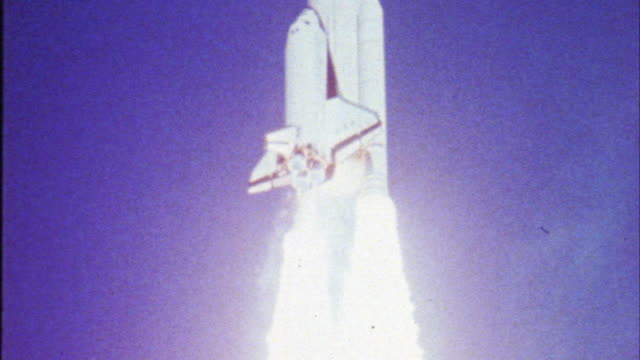 up angle as rocket or space shuttle travels towards space. blue sky and clouds. flames and smoke left as exhaust. saturn v rocket. spaceships. nasa. fire or flames trail behind. - razzo spaziale video stock e b–roll