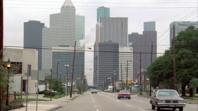 pan left to right on city street out side of downtown houston as cars or traffic drives by. urban area. high rises and city skyline in bg. - 1986 stock videos and b-roll footage