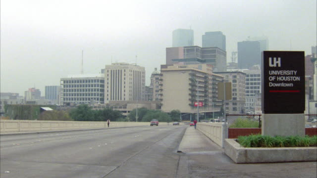 "PAN RIGHT TO LEFT OF HOUSTON SKYLINE TO CITY STREET NEAR ""UNIVERSITY OF HOUSTON DOWNTOWN"" SIGN. RED GMC JIMMY SUV DRIVES BY, MAKES U-TURN, AND HEADS BACK IN OTHER DIRECTION."