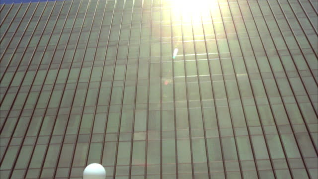 """stockvideo's en b-roll-footage met pan down from up angle to top roof of office building with sun shinning directly into camera to """"computrex corp"""" sign in front of glass office building.  matches r773-2 r773-3 - opeenvolgende serie"""