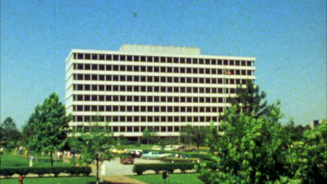 vidéos et rushes de zoom in on nasa building in houston. camera zooms in to upper floor window. windy day. trees. parking lot with cars below. - 1985