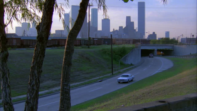 pan right to left from highway, freeway, or street leaving downtown houston as red gmc jimmy suv drives by. passes school on right. telephone poles. overpass. - anno 1987 video stock e b–roll