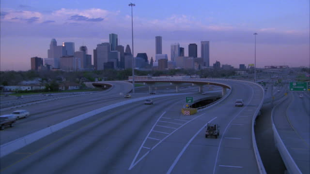 vídeos de stock, filmes e b-roll de pan up from cars driving on street, freeway, or highway to downtown houston skyline. blue sky and clouds. overpasses. - sudoeste dos estados unidos
