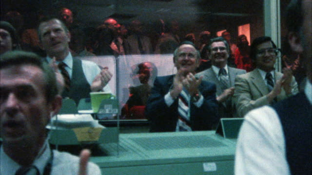 medium angle of nasa control center or control room. men applauding and cheering as they look at monitors. - sala di controllo video stock e b–roll