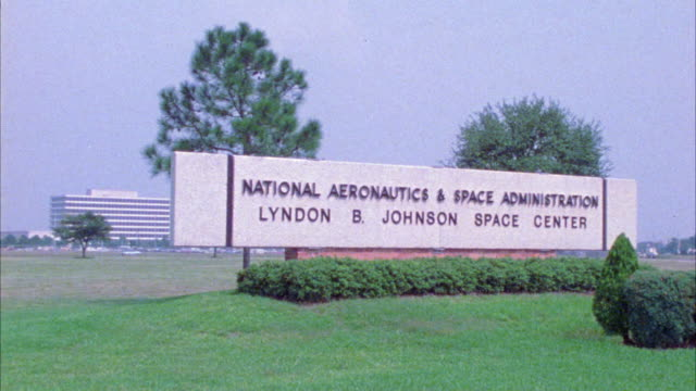 "medium angle of sign reading ""national aeronautics and space administration"" or nasa. lyndon b johnson space center. office building in bg. - nasa video stock e b–roll"